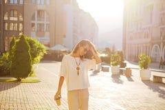 Ευτυχής γυναίκα που περπατά στην πόλη το θερινό πρωί στοκ εικόνες