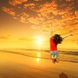Ευτυχής γυναίκα που πηδά στο ηλιοβασίλεμα παραλιών Στοκ Εικόνα