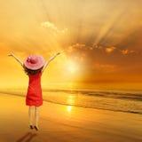 Ευτυχής γυναίκα που πηδά στο ηλιοβασίλεμα παραλιών Στοκ Φωτογραφία