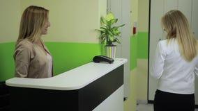 Ευτυχής γυναίκα που πληρώνει με την πιστωτική κάρτα στο σαλόνι SPA φιλμ μικρού μήκους