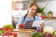 Ευτυχής γυναίκα που προετοιμάζει τα λαχανικά στην κουζίνα στη συνταγή με Στοκ φωτογραφία με δικαίωμα ελεύθερης χρήσης