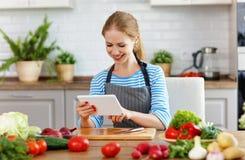 Ευτυχής γυναίκα που προετοιμάζει τα λαχανικά στην κουζίνα στη συνταγή με Στοκ Εικόνες