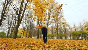 Ευτυχής γυναίκα που ρίχνει επάνω στα πεσμένα φύλλα σφενδάμου απόθεμα βίντεο
