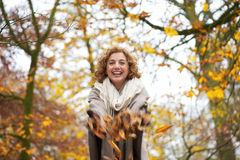 Ευτυχής γυναίκα που ρίχνει τα φύλλα Στοκ φωτογραφία με δικαίωμα ελεύθερης χρήσης