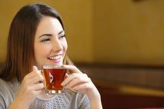 Ευτυχής γυναίκα που σκέφτεται το κράτημα ενός φλυτζανιού του τσαγιού σε μια καφετερία