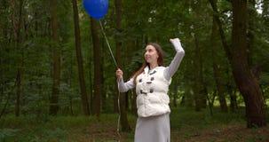 Ευτυχής γυναίκα που στέκεται και που χτυπά ένα μπλε μπαλόνι σε ένα ξύλο την άνοιξη στην slo-Mo απόθεμα βίντεο