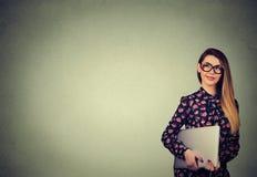 Ευτυχής γυναίκα που στέκεται με το lap-top πέρα από το γκρίζο υπόβαθρο τοίχων Στοκ φωτογραφία με δικαίωμα ελεύθερης χρήσης