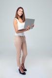 Ευτυχής γυναίκα που στέκεται με το lap-top Στοκ Φωτογραφίες