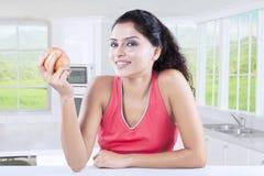 Ευτυχής γυναίκα που τρώει την κόκκινη Apple Στοκ εικόνα με δικαίωμα ελεύθερης χρήσης