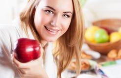 Ευτυχής γυναίκα που τρώει τη Apple Στοκ Φωτογραφία