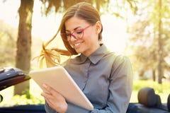 Ευτυχής γυναίκα που υπερασπίζεται το αυτοκίνητό της που χρησιμοποιεί τον υπολογιστή μαξιλαριών που κοιτάζει βιαστικά Διαδίκτυο στοκ εικόνα με δικαίωμα ελεύθερης χρήσης