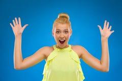 Ευτυχής γυναίκα που φαίνεται έκπληκτη με τα χέρια επάνω. Στοκ Εικόνες