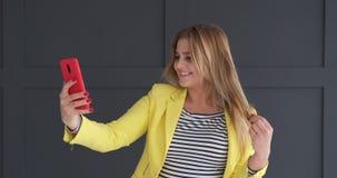 Ευτυχής γυναίκα που φυσά ένα φιλί ενώ βίντεο που κουβεντιάζει στο κινητό τηλέφωνο απόθεμα βίντεο