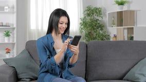 Ευτυχής γυναίκα που χρησιμοποιεί ένα έξυπνο τηλέφωνο σε έναν καναπέ φιλμ μικρού μήκους