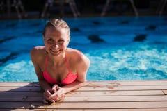 Ευτυχής γυναίκα που χρησιμοποιεί ένα έξυπνο τηλέφωνο σε ένα poolside της λίμνης κήπων της το καλοκαίρι Στοκ φωτογραφίες με δικαίωμα ελεύθερης χρήσης