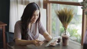 Ευτυχής γυναίκα που χρησιμοποιεί την πιστωτική κάρτα να ψωνίσει on-line με την ταμπλέτα στο café φιλμ μικρού μήκους
