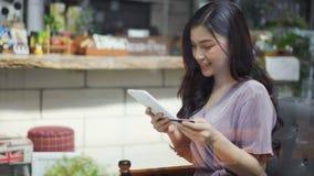 Ευτυχής γυναίκα που χρησιμοποιεί την πιστωτική κάρτα να ψωνίσει on-line με την ταμπλέτα στο café απόθεμα βίντεο