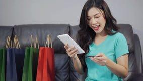 Ευτυχής γυναίκα που χρησιμοποιεί την ψηφιακή ταμπλέτα για on-line να ψωνίσει με την πιστωτική κάρτα στο καθιστικό απόθεμα βίντεο
