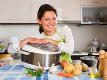 Ευτυχής γυναίκα που χρησιμοποιεί την slo-κουζίνα Στοκ Φωτογραφίες