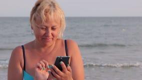 Ευτυχής γυναίκα που χρησιμοποιεί το τηλέφωνο που επικοινωνεί στο διαδίκτυο ενάντια στο σκηνικό των κυμάτων θάλασσας απόθεμα βίντεο