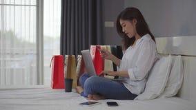 Ευτυχής γυναίκα που χρησιμοποιεί το φορητό προσωπικό υπολογιστή για on-line να ψωνίσει με την πιστωτική κάρτα στο κρεβάτι απόθεμα βίντεο