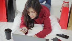 Ευτυχής γυναίκα που χρησιμοποιεί το φορητό προσωπικό υπολογιστή για on-line να ψωνίσει με την πιστωτική κάρτα στο κρεβάτι φιλμ μικρού μήκους