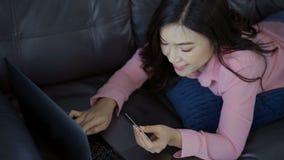 Ευτυχής γυναίκα που χρησιμοποιεί το φορητό προσωπικό υπολογιστή για on-line να ψωνίσει με την πιστωτική κάρτα στο καθιστικό φιλμ μικρού μήκους