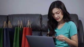 Ευτυχής γυναίκα που χρησιμοποιεί το φορητό προσωπικό υπολογιστή για on-line να ψωνίσει με την πιστωτική κάρτα στο καθιστικό απόθεμα βίντεο