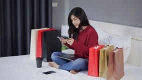 Ευτυχής γυναίκα που χρησιμοποιεί το smartphone για on-line να ψωνίσει με την πιστωτική κάρτα στο κρεβάτι απόθεμα βίντεο