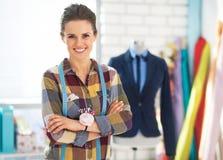 Ευτυχής γυναίκα ραφτών μπροστά από το μανεκέν Στοκ Εικόνες