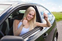 Ευτυχής γυναίκα σε ένα αυτοκίνητο που παρουσιάζει ένα κλειδί στοκ εικόνες με δικαίωμα ελεύθερης χρήσης