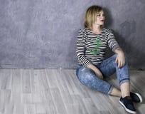 Ευτυχής γυναίκα σε μια ριγωτή μπλούζα και τα τζιν που κάθεται στο ξύλινο πάτωμα στοκ εικόνες με δικαίωμα ελεύθερης χρήσης