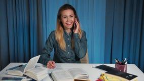 Ευτυχής γυναίκα σπουδαστής σε ένα πουκάμισο τζιν, που μιλά σε ένα smartphone η στιγμή όταν κάνει την εργασία Γράφει στο α απόθεμα βίντεο