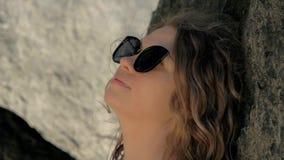 Ευτυχής γυναίκα στα γυαλιά ηλίου που στηρίζονται το άπαχο κρέας πίσω στο βουνό στη θερινή ημέρα Χαλαρώνοντας κορίτσι που κλίνει π απόθεμα βίντεο