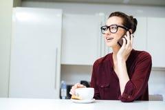 Ευτυχής γυναίκα στα γυαλιά που μιλούν στο τηλέφωνο κυττάρων στην κουζίνα στοκ φωτογραφία