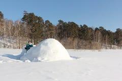 Ευτυχής γυναίκα στα θερμά ενδύματα που στέκονται κοντά στην παγοκαλύβα σε ένα ξέφωτο χιονιού το χειμώνα, Σιβηρία, Ρωσία στοκ φωτογραφίες
