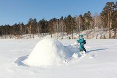 Ευτυχής γυναίκα στα θερμά ενδύματα που στηρίζεται μια παγοκαλύβα σε ένα ξέφωτο χιονιού το χειμώνα, Σιβηρία, Ρωσία στοκ εικόνα με δικαίωμα ελεύθερης χρήσης
