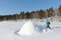 Ευτυχής γυναίκα στα θερμά ενδύματα που στηρίζεται μια παγοκαλύβα σε ένα ξέφωτο χιονιού το χειμώνα, Σιβηρία, Ρωσία στοκ εικόνα