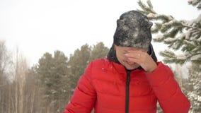 Ευτυχής γυναίκα στα κόκκινα ενδύματα με το χιόνι στο πρόσωπό της που χαμογελά μετά από να πέσει στο χιόνι στο χειμερινό δάσος απόθεμα βίντεο