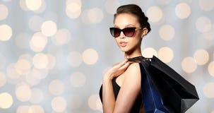 Ευτυχής γυναίκα στα μαύρα γυαλιά ηλίου με τις τσάντες αγορών Στοκ φωτογραφίες με δικαίωμα ελεύθερης χρήσης