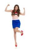 Ευτυχής γυναίκα στα υψηλά τακούνια και το μίνι φόρεμα ενθαρρυντικά στοκ εικόνα