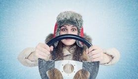 Ευτυχής γυναίκα στα χειμερινά ενδύματα με ένα τιμόνι, χιονοθύελλα χιονιού Οδηγός αυτοκινήτων έννοιας Στοκ Εικόνες
