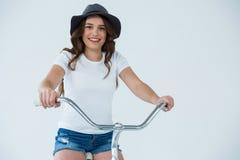 Ευτυχής γυναίκα στην άσπρη μπλούζα και καυτά εσώρουχα στο ποδήλατο Στοκ Φωτογραφία