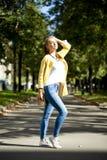 Ευτυχής γυναίκα στην κίτρινη οδό φθινοπώρου περπατήματος παλτών Στοκ Φωτογραφία