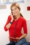Ευτυχής γυναίκα στην κόκκινη ομιλία στο τηλέφωνο στο σπίτι στοκ φωτογραφία