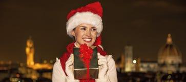 Ευτυχής γυναίκα στη Φλωρεντία, Ιταλία με το δώρο Χριστουγέννων που κοιτάζει κατά μέρος Στοκ φωτογραφία με δικαίωμα ελεύθερης χρήσης
