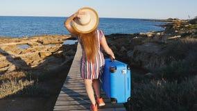 Ευτυχής γυναίκα στις διακοπές που τρέχουν με τη βαλίτσα απόθεμα βίντεο