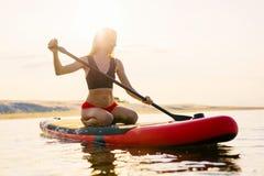 Ευτυχής γυναίκα στον πίνακα κουπιών στο ηλιοβασίλεμα στοκ φωτογραφία