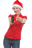 Ευτυχής γυναίκα στο καπέλο Χριστουγέννων που δείχνει σε κινητό Στοκ Φωτογραφία