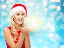 Ευτυχής γυναίκα στο καπέλο santa με τη σκόνη νεράιδων στους φοίνικες Στοκ Εικόνα